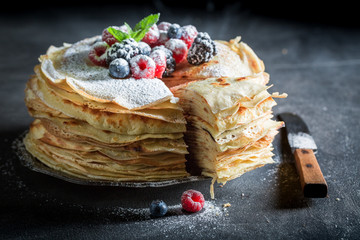 Piece of pancakes cake with berries and powdered sugar
