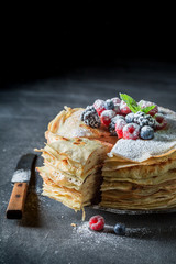Closeup of stack of pancakes with fresh berries and sugar