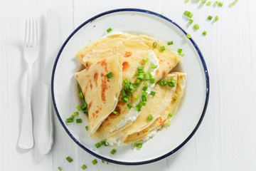 Pancakes with cottage cheese and chive on white table