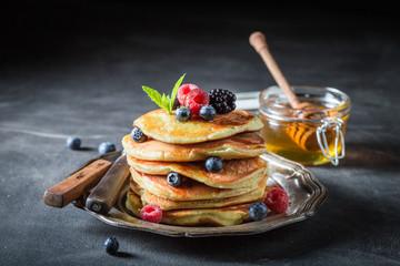 American pancakes with blueberries and raspberries on dark table