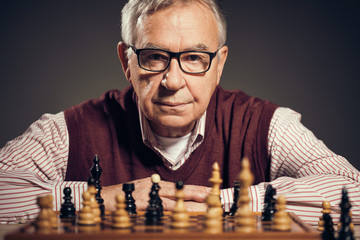 Portrait of senior man who is participating in chess game.