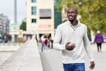 Black young man with a smartphone in his hand in urban background