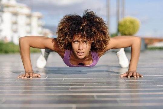 Black fit woman doing pushups on urban floor.