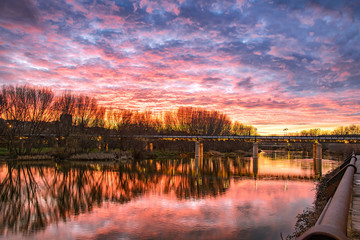 Wall Murals Water lilies Magical sunset with magenta tones over river and iron bridge