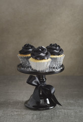 Three cup cakes with black buttercream topping on a cake stand