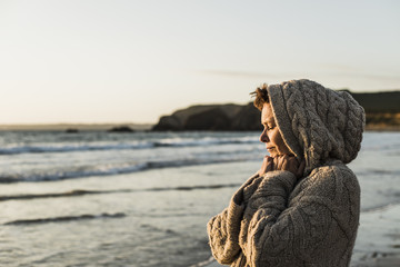France, Crozon peninsula, woman wearing a cardigan on the beach at sunset