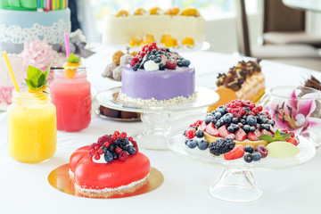Many sweet pastries on white table with fresh summer berries. Festive table settings. Light background. Shallow depth of field