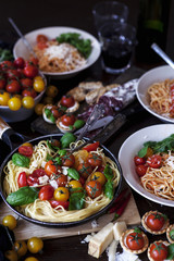 Prepared spaghetti with tomatoes, basil leaves and parmesan