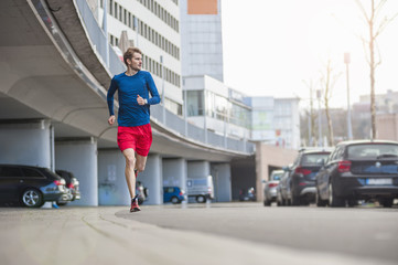 Young sporty man jogging on road