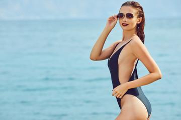 slim attractive woman posing in blue waters of Adriatic sea beach