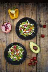 Salad bowls with lamb's lettuce, quinoa, yellow bell pepper, cocktail tomato, avocado, feta and pomegranate seeds