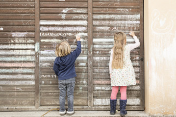 Back view of two little girls drawing on an old garage door