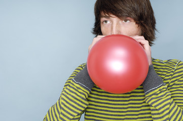 Teenage boy blowing red balloon in front of blue background
