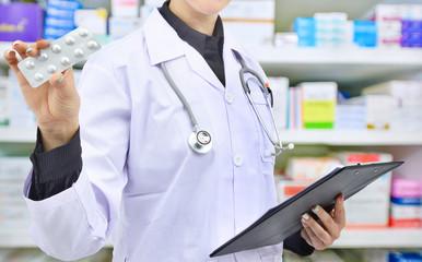 Pharmacist holding medicine capsule and prescription chart for filling prescription in pharmacy drugstore