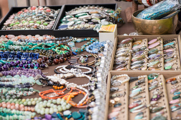 Shot of expensive gemstone jewelry. Rings, necklaces and bracelets made of peridot and azurite stones, red coral, sapphire, rose quartz and moonstone. Powerful, healing crystals, luxury background