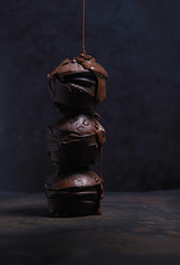 Liquid chocolate dripping on stack of three chocolate muffins