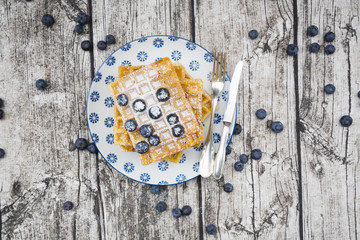 Plate of waffles with icing sugar and blueberries