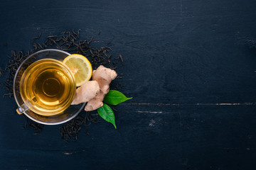 Tea with lemon and ginger. Hot drink On a wooden background. Top view. Copy space.