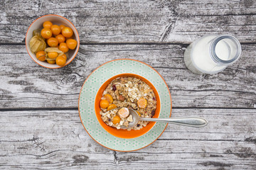 Bowl with cereals and physalis, milk bottle on wood