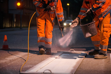 Traffic line painting. Workers are painting white street lines on pedestrian crossing. Road cones with orange and white stripes in background, standing on asphalt during road construction works.