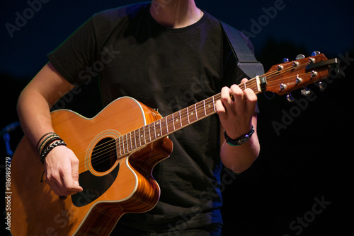 Macro Shot Of Boy Playing Acoustic Guitar On Stage On Evening Band