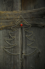 Christmas tree shaped of chains on wood