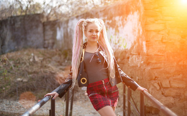 A girl with dreadlocks in a leather jacket and a short skirt stands against the background of an old stone wall in the rays of a bright sun