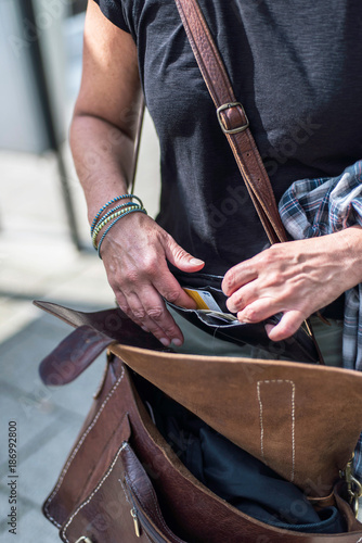 Female hands inspecting wallet while standing at train