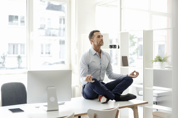 Businessman sitting on table in office practising yoga