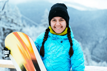 woman stands with snowboard on the top of the hill