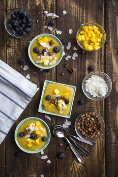 Bowls of mango smoothie with diced mango, coconut flakes, blueberries and chocolate crunch