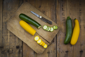 Whole and sliced yellow and green zucchini on wood