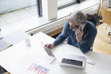 Mature man working in office with smart phone and digital tablet