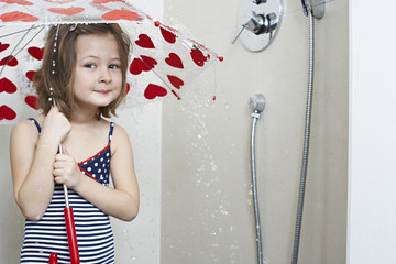 Portrait of smiling little girl taking shower with umbrella