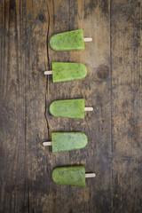 Row of homemade kiwi ice lollies on dark wood