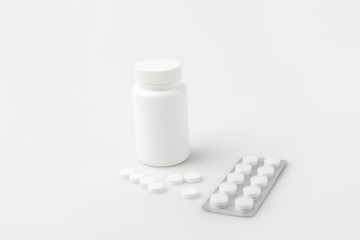 container, scattered pills  and tablets in package isolated on white background