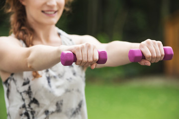 Similng woman holding dumbbells