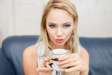 Young blonde woman drinking coffee indoors