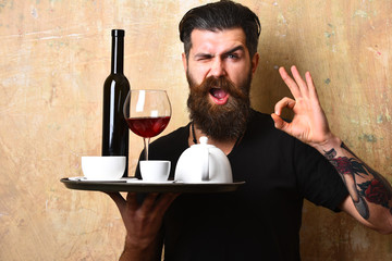 Man with beard holds various drinks on beige wall background