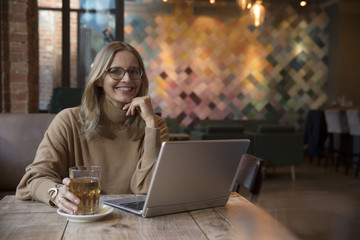 Portrait of laughing businesswoman with laptop in a restaurant