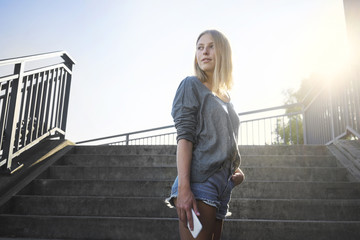 Blond young woman with smartphone standing at backlight in front of stairs