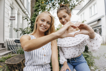Two smiling young women shaping heart with their hands in the city
