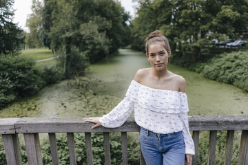 Portrait of young woman standing on a bridge