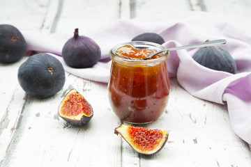Organic figs and a glass of fig jam on a wood
