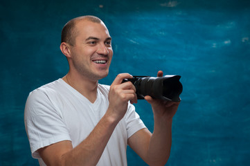 Portrait of smiling middle-aged man in white shirt with camera in his hands posing on blue background. Copyspace