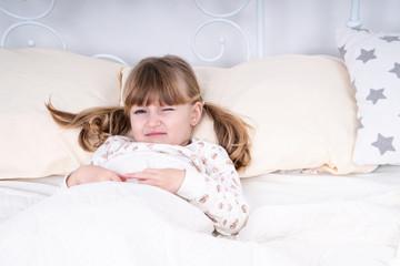 Girl winks with one eye lying in bed under the blanket, preparing to sleep