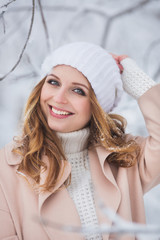 Portrait of smiling young woman in a beige coat and white hat in a winter
