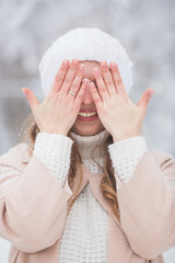 Portrait of smiling young pretty woman with closed eyes in a winter