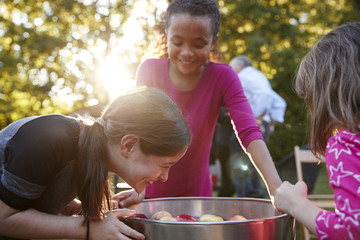 Young girls laugh while apple bobbing at a backyard party