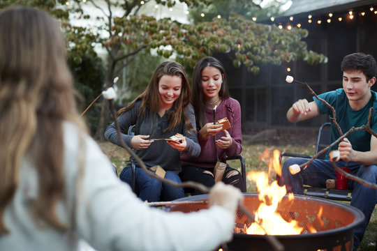 Teenage friends making sÕmores with toasted marshmallows